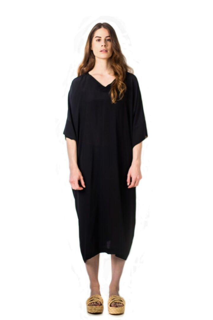 Robe inspirée du caftan avec forme rectangulaire entièrement confectionnée en crêpe de soie noire par la maison TREMBLEPIERRE.